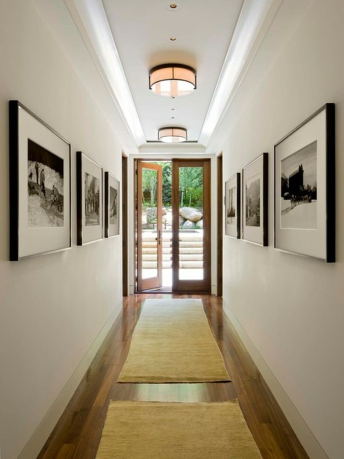 six large square frames, containing black and white images, mounted on two opposite walls of a corridor, hallway decorating ideas, dark wooden floors, two beige rugs