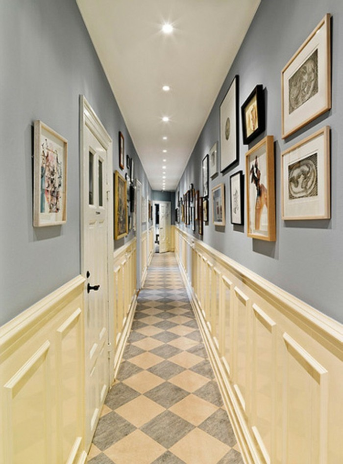 hallway design ideas, long narrow corridor, pale blue-grey walls, with cream white paneling, and many framed images, white ceiling with inbuilt lights, tiled floor and white doors