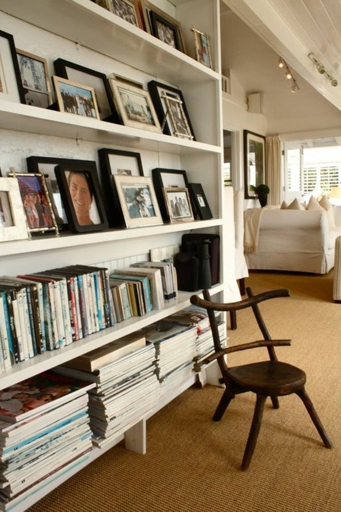 books and many framed photos, on white shelves, near a small wooden chair, hallway furniture ideas, beige carpet