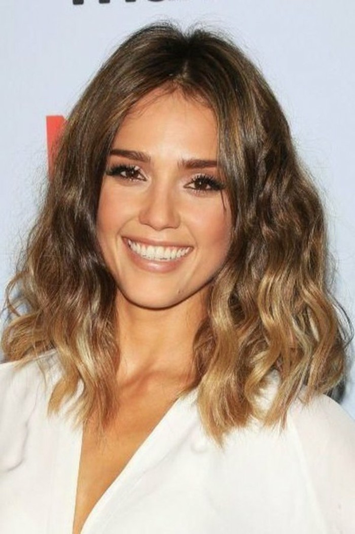 white v-neck top, worn by smiling jessica alba, with black mascara and nude lipstick, medium length brown hair, with blonde highlights