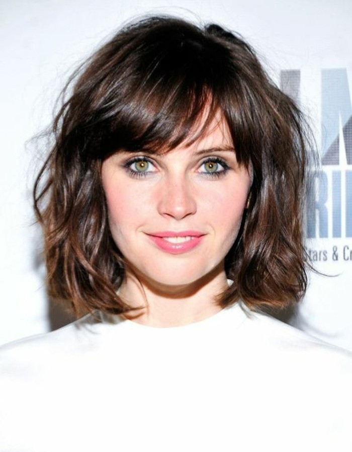 shaggy wavy bob, with side-pated bangs, on smiling woman, with hazel eyes and pale pink lipstick, medium brown hair color, wearing white top