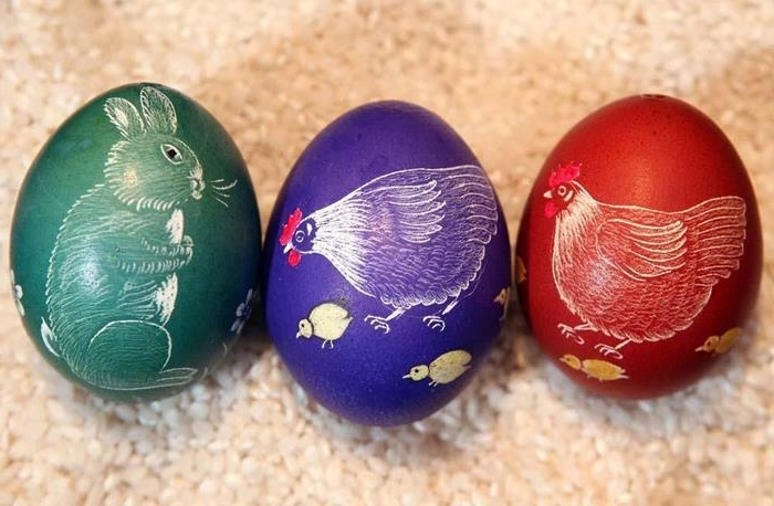 mother hens with chicks, and a bunny, drawn on three easter eggs, dyed in red, violet and green