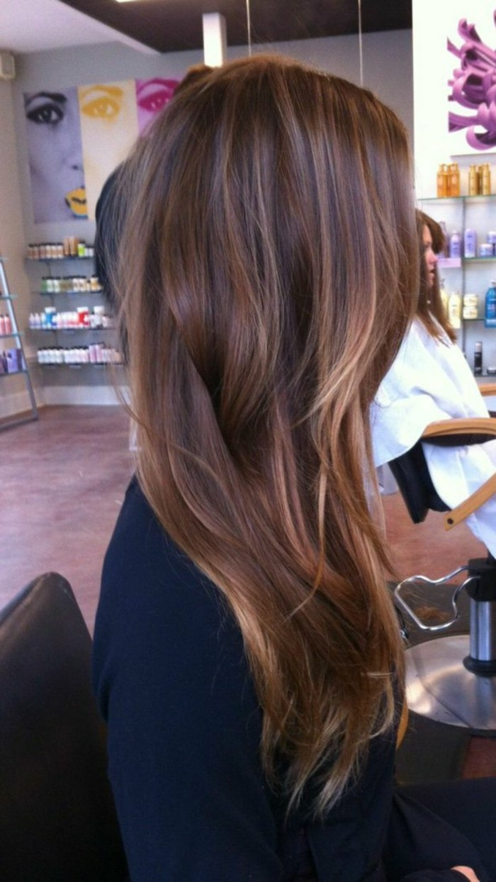 soft layered and wavy, long brown highlighted hair, with natural looking blonde strands, worn by woman in black sweater, sitting on hairdresser's chair