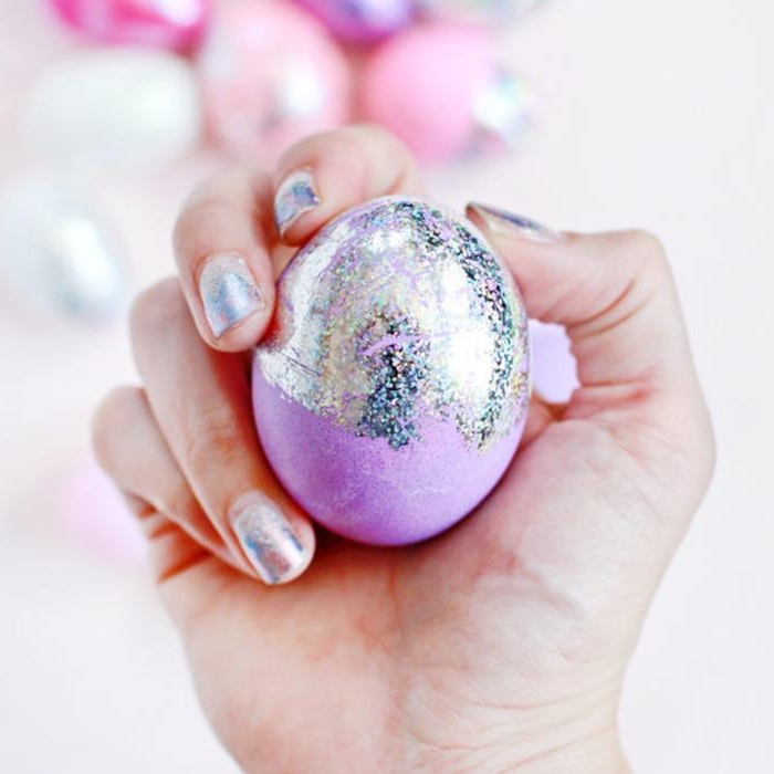 pale purple egg, partially covered with iridescent, hologram-like paint, easter egg designs, held by a hand with matching nail polish