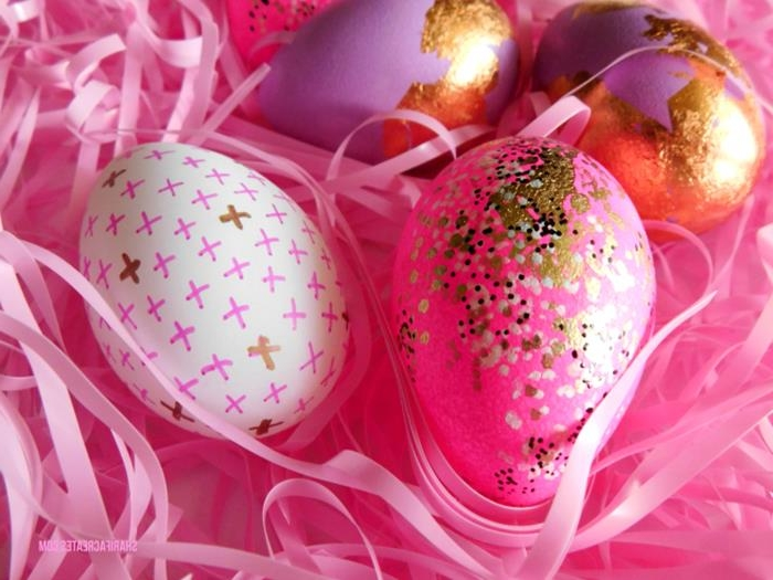 hot pink easter eggs, decorated with white, black and golden dots, or gold leaf, and one white egg, decorated with pink and gold crosses, pink easter grass