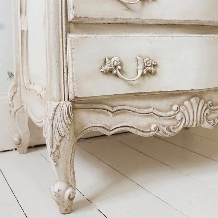 close up of ornamental details, on worn antique dresser, painted in aged cream color, country cottage furniture, white wooden floor