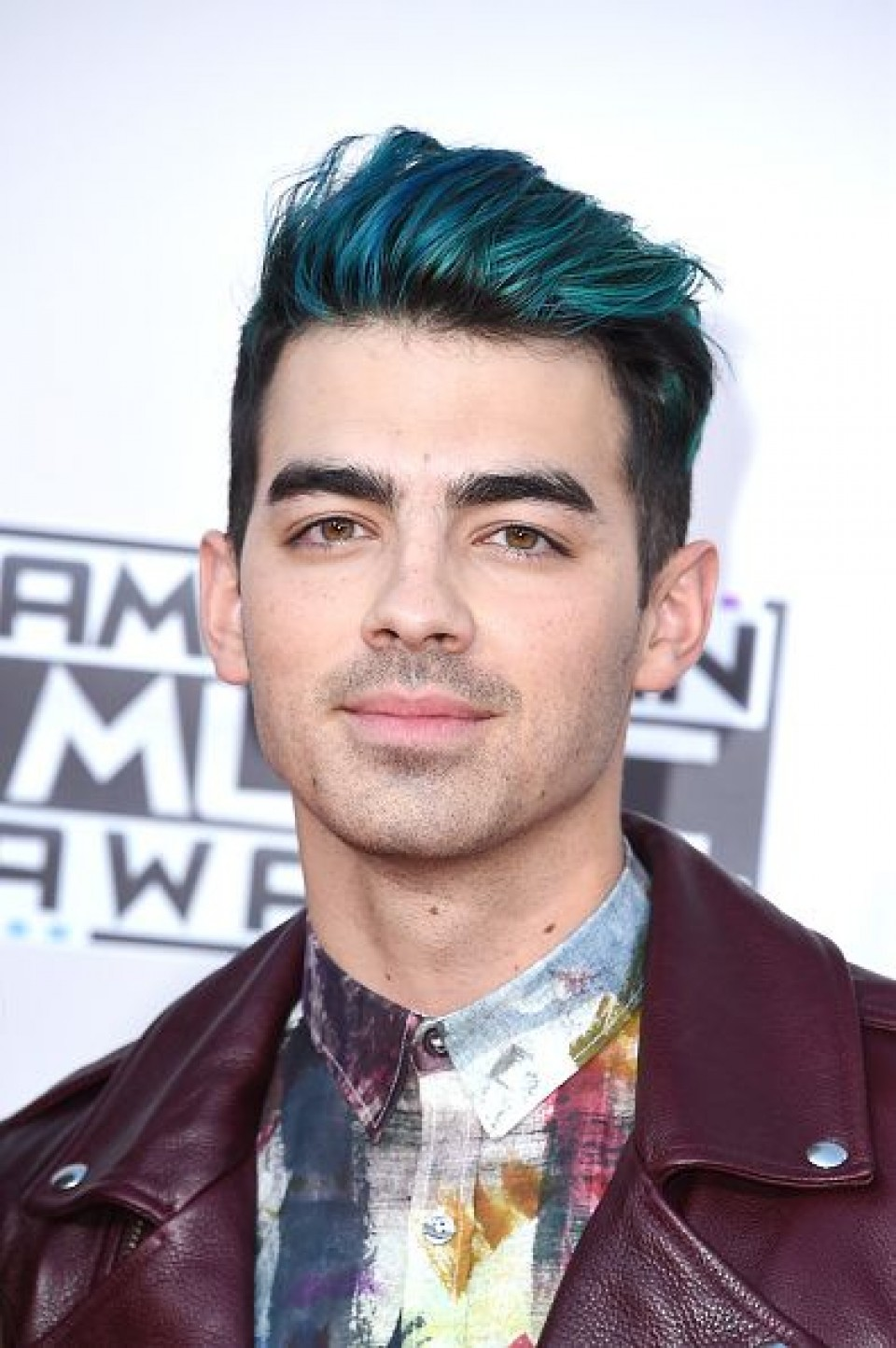 electric blue dyed hair, with long slicked back bangs, and shorter sides, worn by joe jonas, in a multicolored shirt, and maroon leather jacket