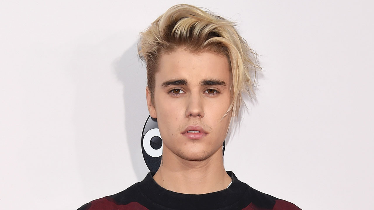 older justin bieber, with chin-length hair, dyed light blonde, with dark roots, bangs swept to one side, long hairstyles for boys