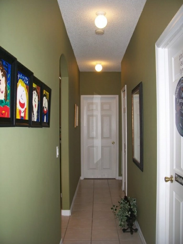 khaki green walls, white ceiling and pale beige floor tiles, inside a corridor with three white doors, small hallway ideas, framed mirror and four children's drawings on walls