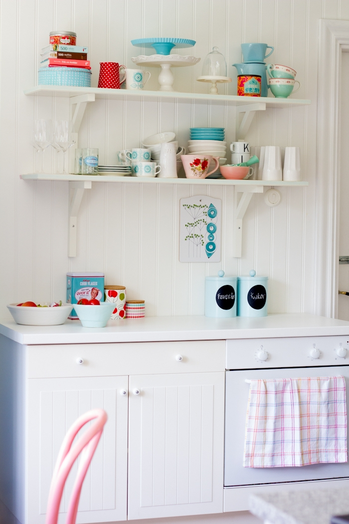 kitchen with white vintage cupboards, two white wooden shelves, shabby chic furniture, various mugs and plates, in pale pastel pink and teal