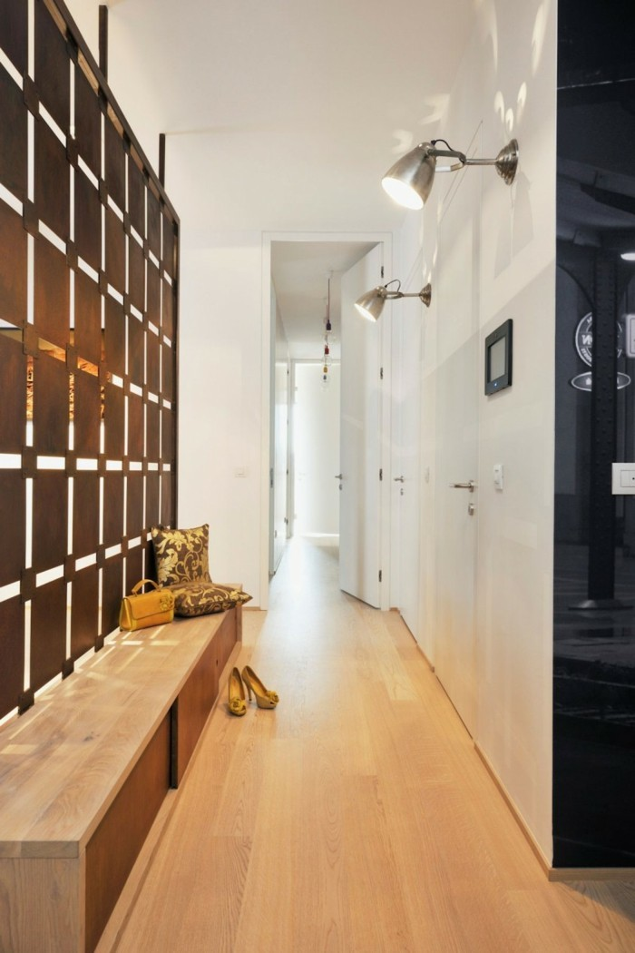 shoe closet made of wood, inside a narrow hallway, with pale laminate floor, small hallway ideas, white walls and doors, brown partition between rooms