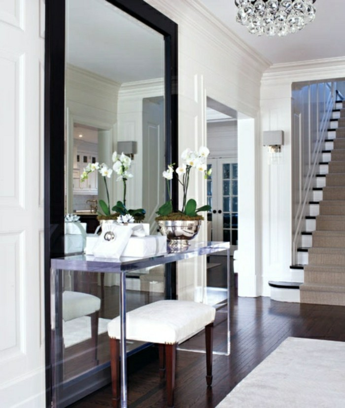large mirror in black frame, on white wall, near metal table with potted plant, hallway decor, dark laminate floor, staircase with beige rug