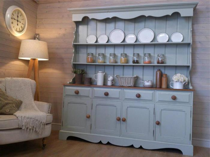 duck's egg blue antique cupboard, with plates and jars, and other kitchen utensils, country chic décor, cream armchair with throw, lamp and wall clock