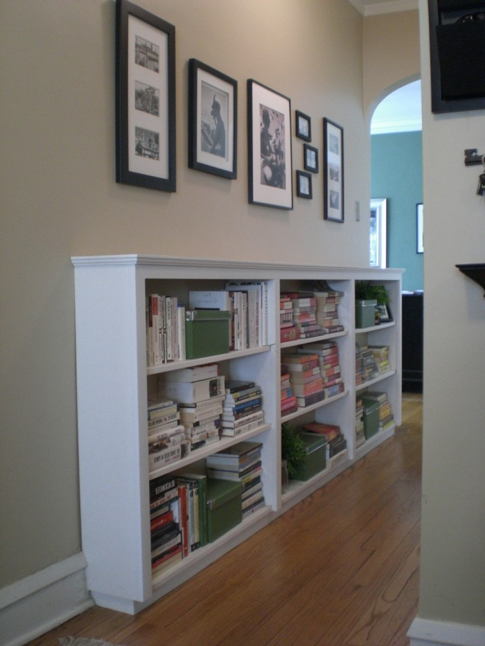 large white cupboard, with shelves containing books and boxes, several photographs in differently sized and colored frames hanging above it, hallway decorating ideas, wooden laminate floor