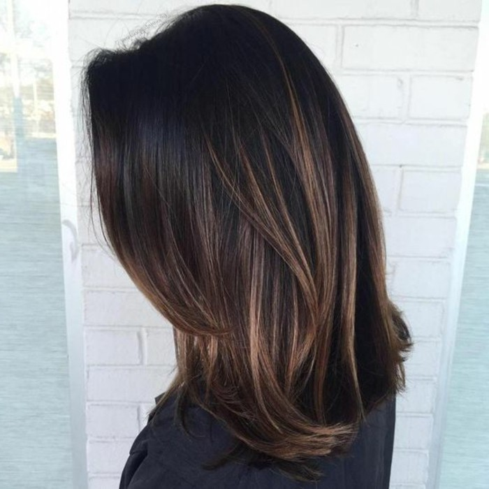 balayage on wavy, layered brown hair, with dark blonde highlights, dark brown hair colors, worn by woman in dark jumper