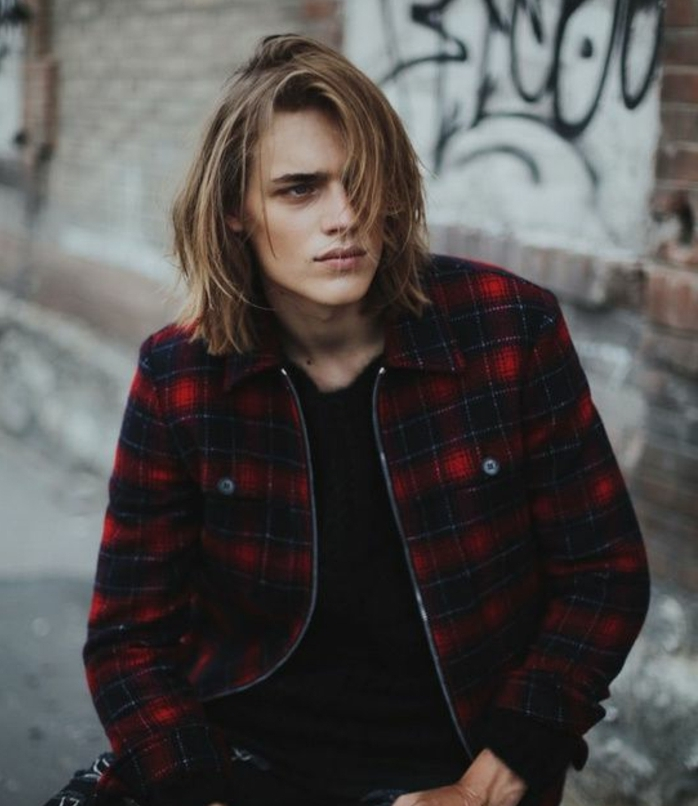 grunge style shoulder-length hair, blonde and layered, long hairstyles for boys, worn by teenager in black jumper, and red plaid jacket
