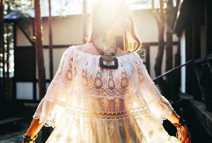 wide frilly lace, boho style tunic, in pale cream, worn with a chunky, tribal necklace and bracelets, by young brunette woman