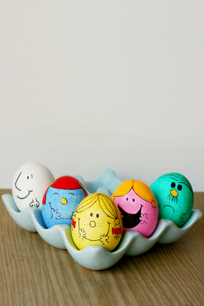 five eggs dyed in teal, pink and yellow, blue and white, made to look like characters from the little miss and mister series, easter egg ideas, inside a grey egg dish