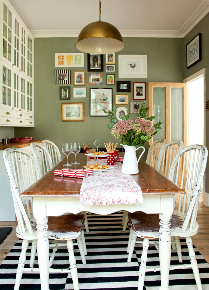 dining room with long wooden table, in white and brown, with matching chairs, shabby chic furniture, green walls with many framed images