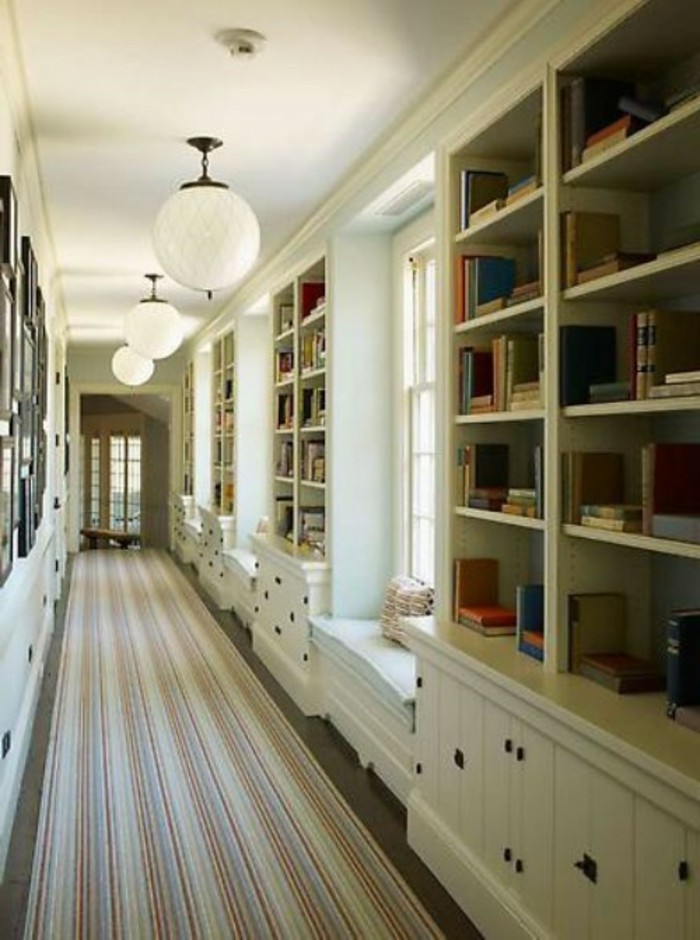 several large white bookshelves, with cupboards underneath, in a long corridor, with white walls, windows and framed images, hallway design ideas, long multicolored striped rug, round ceiling lamps