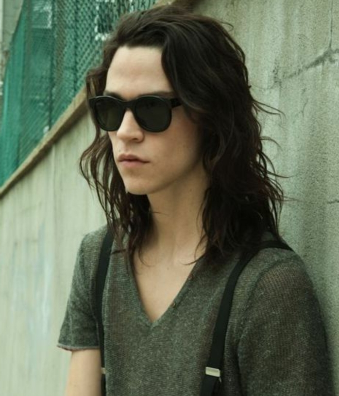 pale youth with black sunglasses, wearing olive green v-neck t-shirt and suspenders, with dark brown and wavy, shoulder length hair, long hairstyles for boys