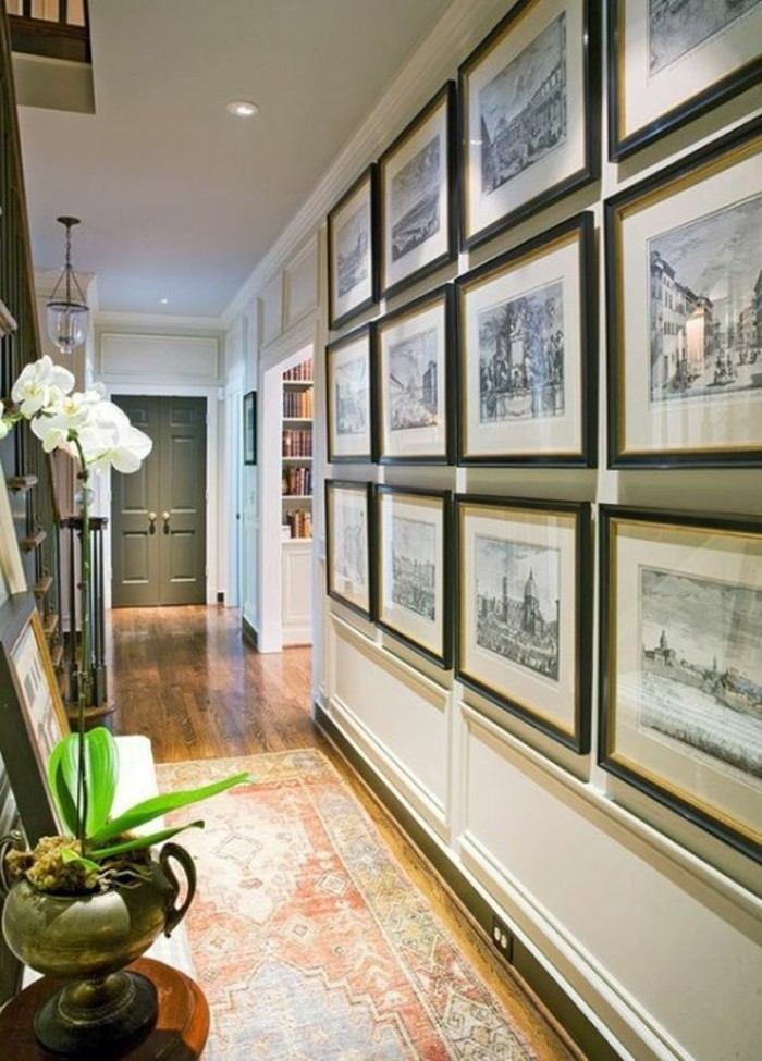 antique looking faded patterned rug, in red and pale blue, in a long corridor, visible wall covered with framed artworks, long hallway runners, potted plants nearby