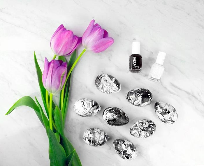 black and white marble effect easter eggs, dyed with nail polish, placed on a marble surface, near three purple tulips, and two bottles of nail polish