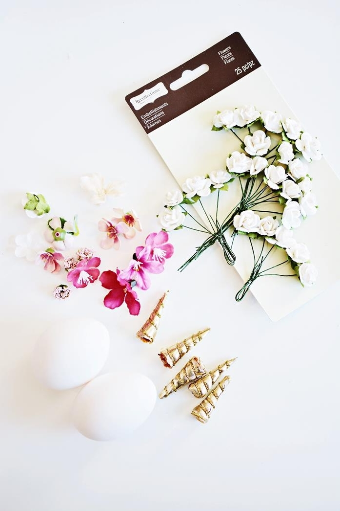unicorn egg materials, small artificial flowers, in white and pink, five fabric horns in gold, two white eggs, dying easter eggs