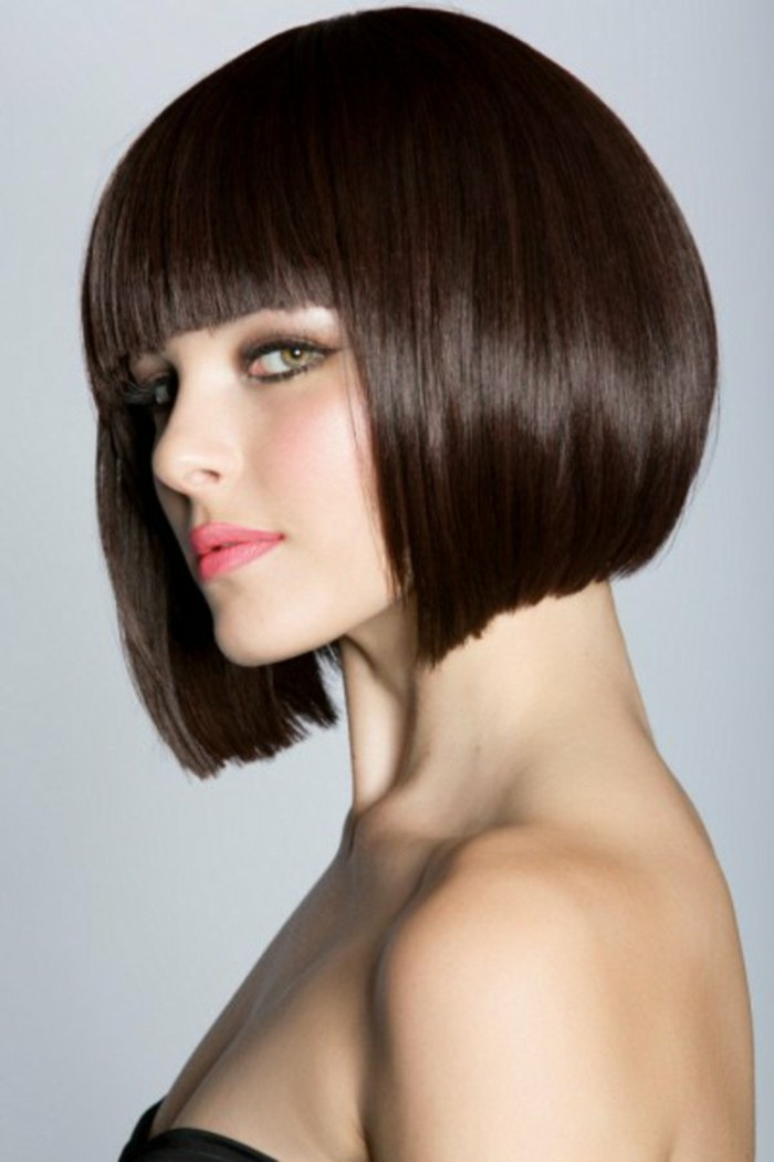 bob with fringe, in dark brunette color, on woman in black strapless top, with coral pink lipstick, and smoky eye make up