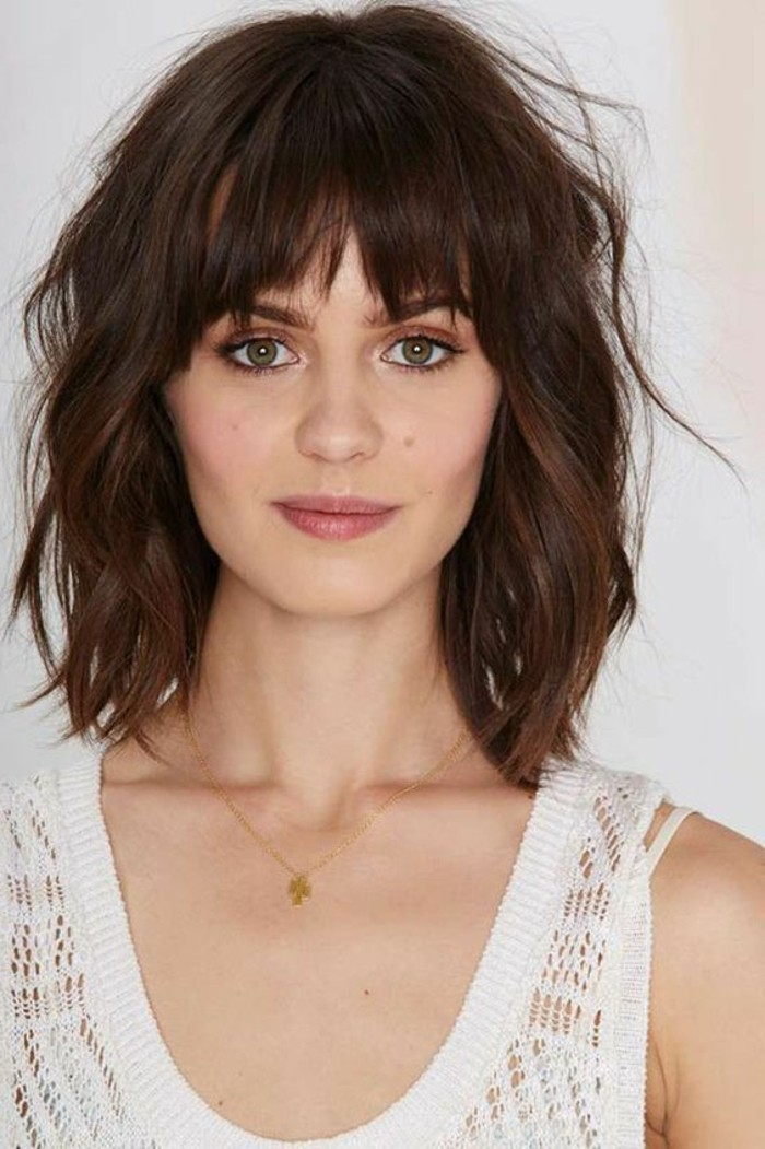 chocolate brown wavy and messy hair, medium brown hair color, and choppy shaggy bangs, on woman with natural looking make up, and green eyes, wearing white meshy tank top