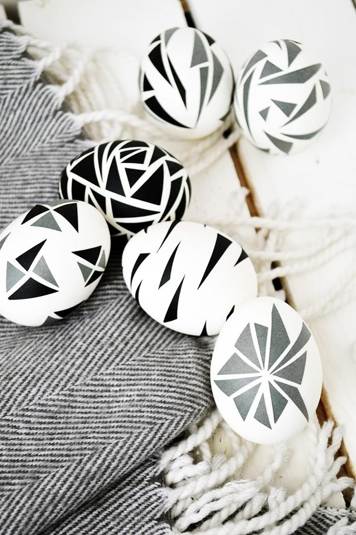 six white eggs, decorated with black and grey triangular shapes, placed on patterned, grey and cream fabric with tassels, dying easter eggs