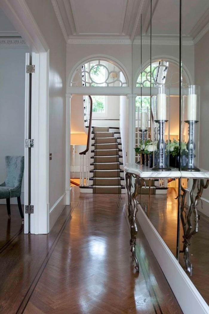 laminate floor, several large wall mirrors, small ornate table with decorations, hallway furniture ideas, staircase in the background