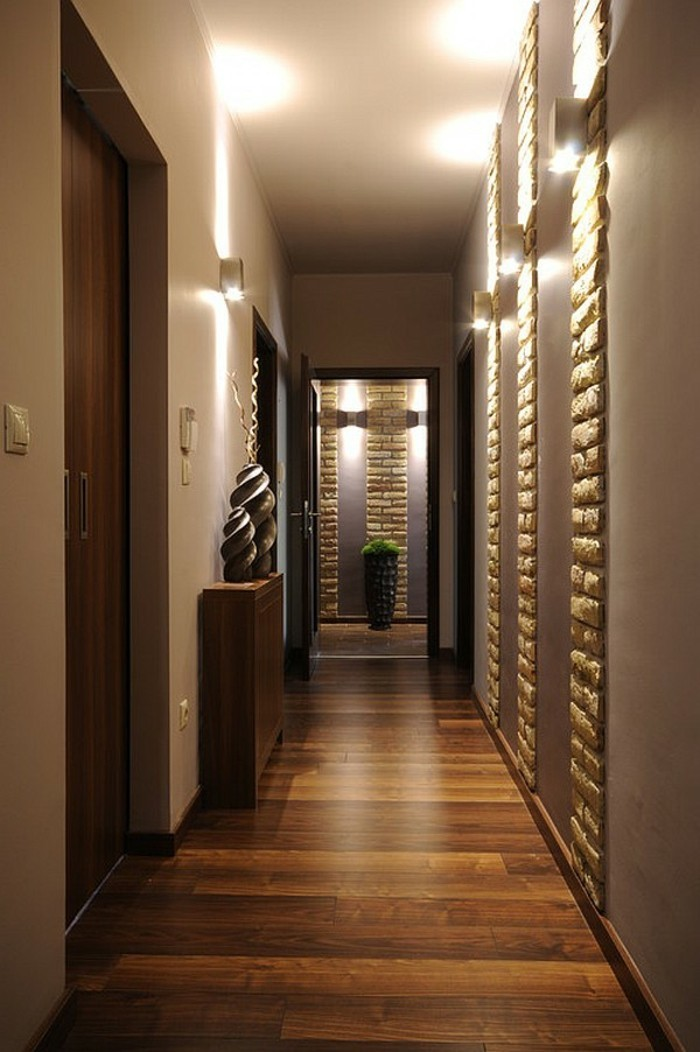 luxurious minimalist hall, with wooden floorboards, inbuilt stone details in walls, hallway design ideas, wooden doors, two sculptures on a brown cupboard, potted plant in background