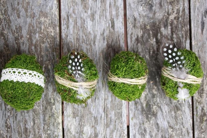 four moss covered eggs, coloring easter eggs, three are tied with sting, two have small quail feathers attached to them, one is decorated with white crochet lace ribbon