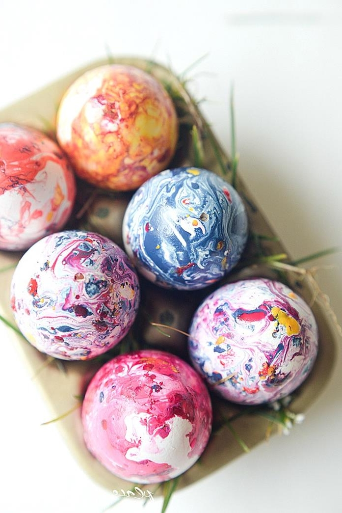 nail polish easter egg coloring, a set of six eggs, dyed in swirly yellow, orange and pink, blue and white, in a cardboard egg box decorated with blades of grass
