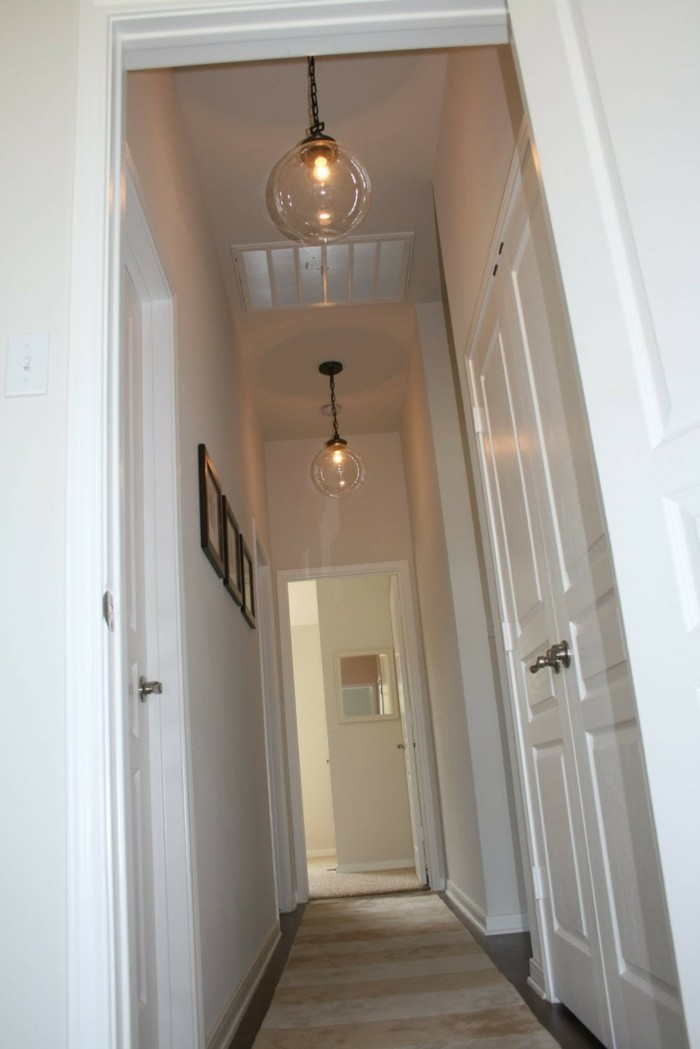 two lit round lamps, made from clear glass, hanging from white ceiling, near two white doors, hallway decor ideas, two white walls, one decorated with three framed images