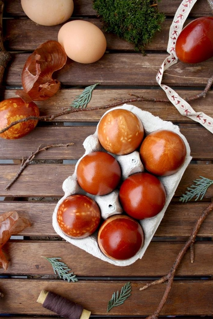 grey cardboard box, containing six naturally dyed eggs, half featuring leaf patterns, easter egg ideas, onion peels and branches, plain eggs and thread