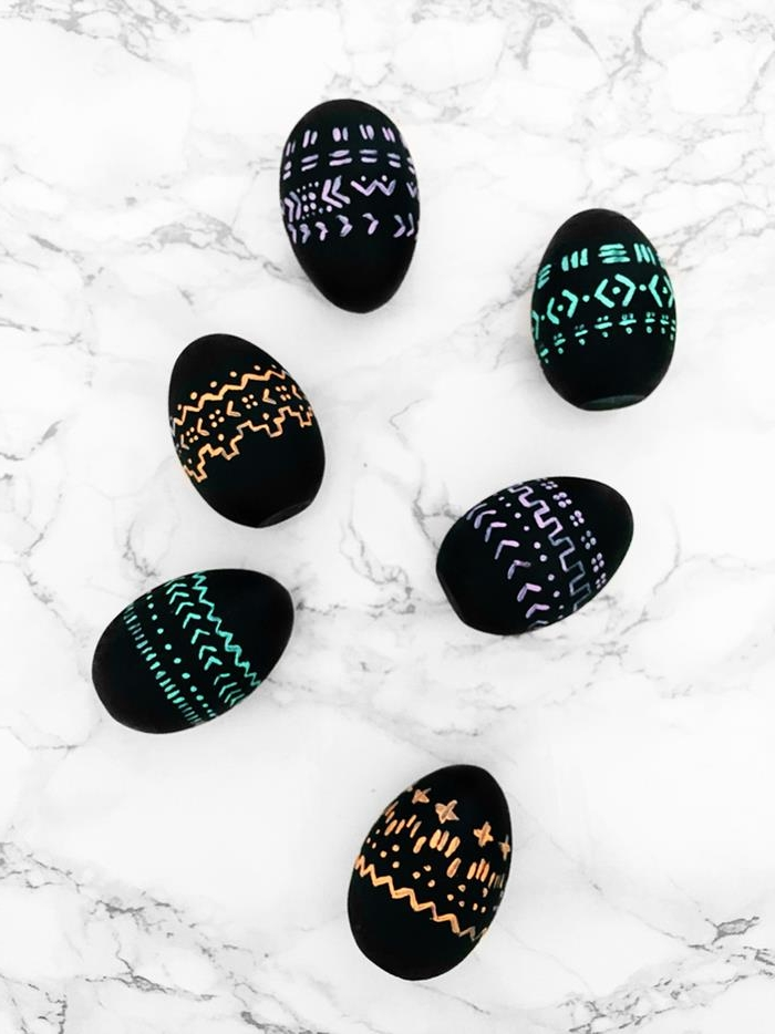 patterns drawn in neon pink, blue and orange, on six black eggs, easter egg ideas, placed on marble surface