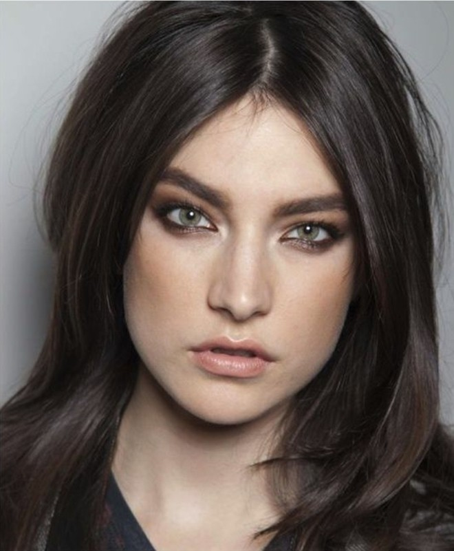 layered hair parted in the middle, dark brown hair colors, worn by green-eyed woman, with smoky eye make up, and nude lipstick
