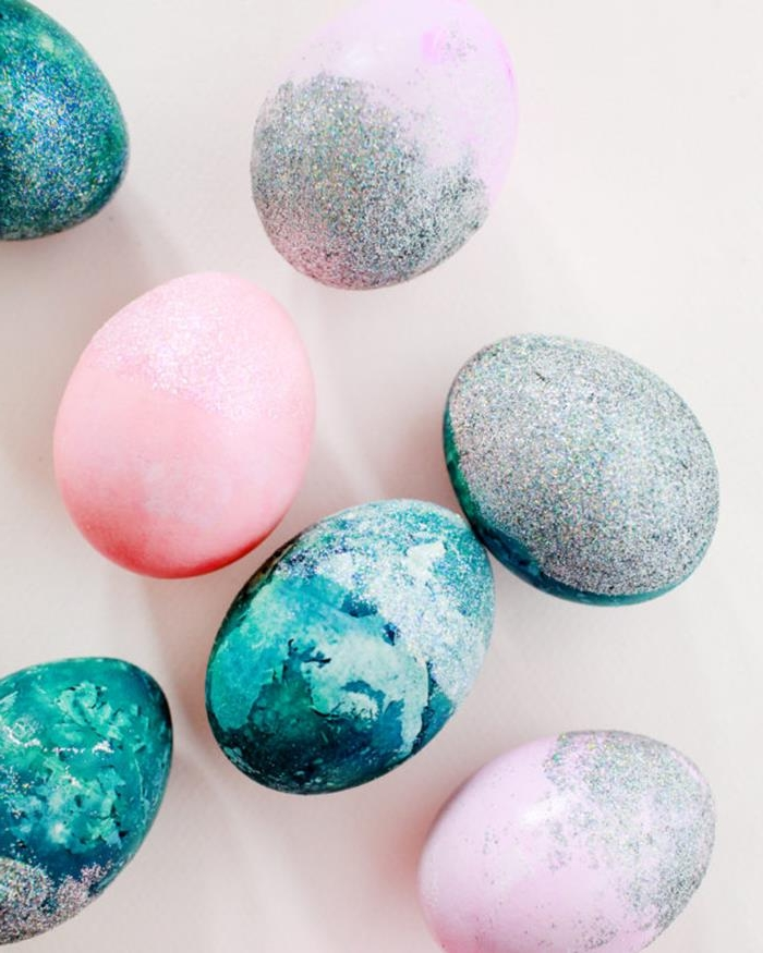 pastel colored easter eggs, in ocean blue and pale pink, some covered in silver iridescent glitter