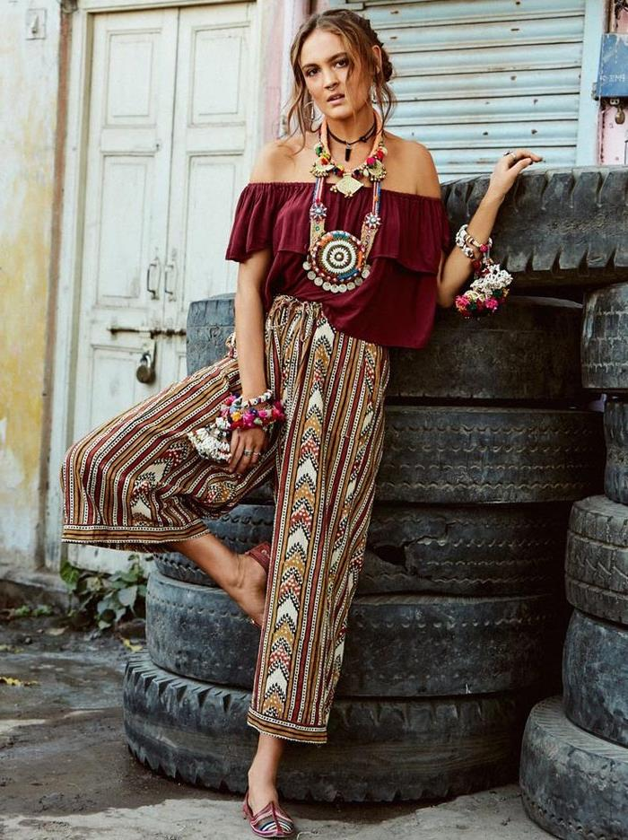 patterned wide trousers, in burgundy red and white, yellow and blue, bohemian style clothing, worn by woman in dark red frilled top, with chunky necklaces and bracelets