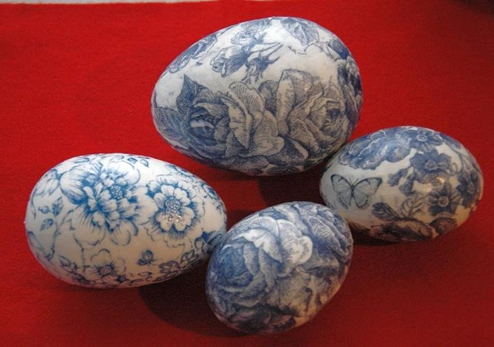 decoupage easter eggs, one large and three smaller, covered in blue floral napkins, with roses and butterflies, intense red background