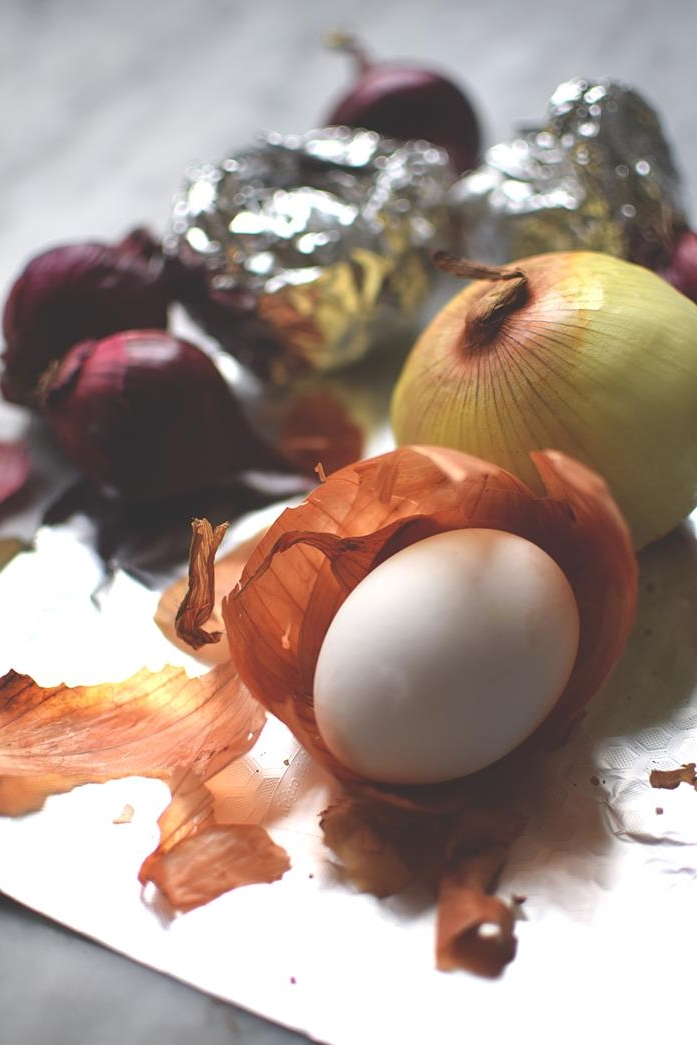 tin foil near red and yellow onions, one white egg, placed in an orange onion peel, easter egg ideas for natural egg dying
