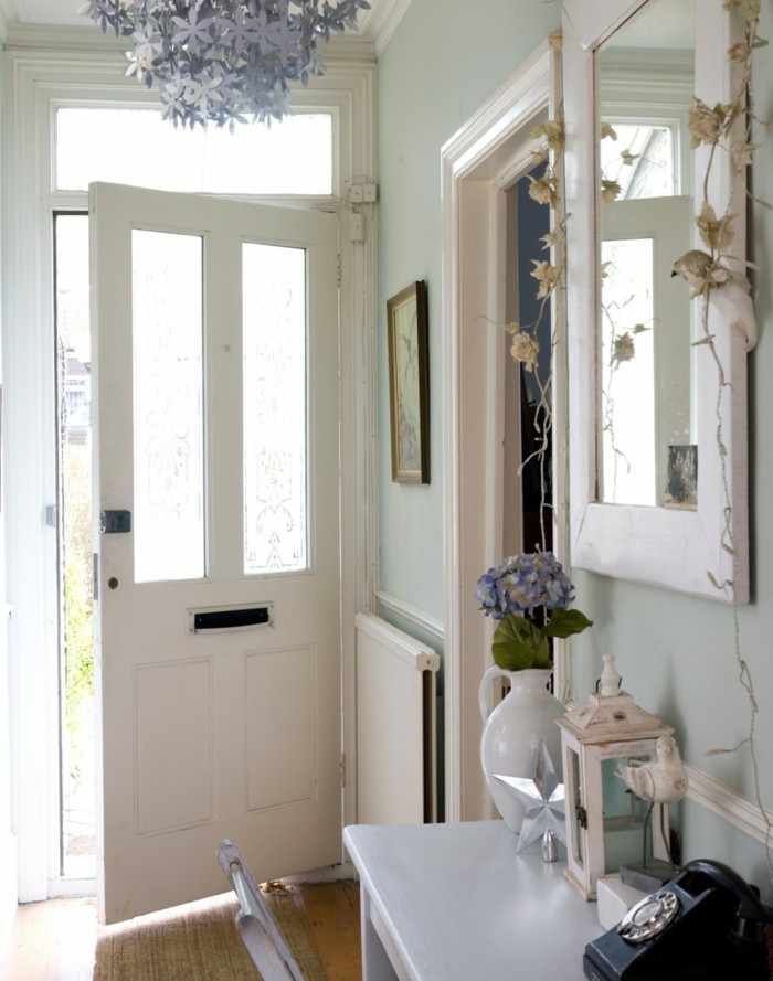 hallway decorating ideas, open white front door, pale blue walls, white plaster details, mirror in white frame, pale grey desk with various items, and matching chair