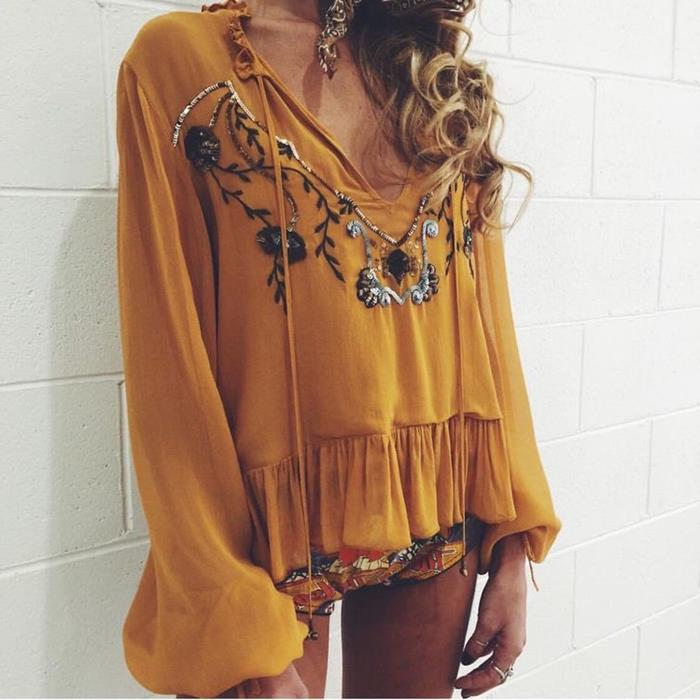 mustard yellow blouse, with long bell sleeves, large frilled hem, and floral embroidery, featuring beads, boho clothing, worn by blonde woman, with curly hair, and multicolored hot pants