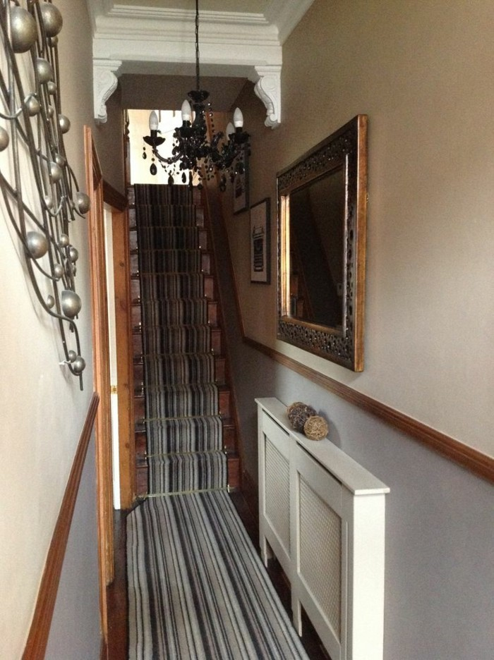 striped rug in pale and dark grey, covering narrow wooden stairs, and continuing on the floor below, long hallway runners, pale beige and grey walls, mirror in ornate frame