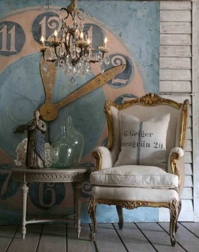 gold and white wing chair, antique shabby chic style, with graphic print cushion, near grey ornamental table, decorated with glass bottles and a statuette, crystal chandelier and a large clock mural