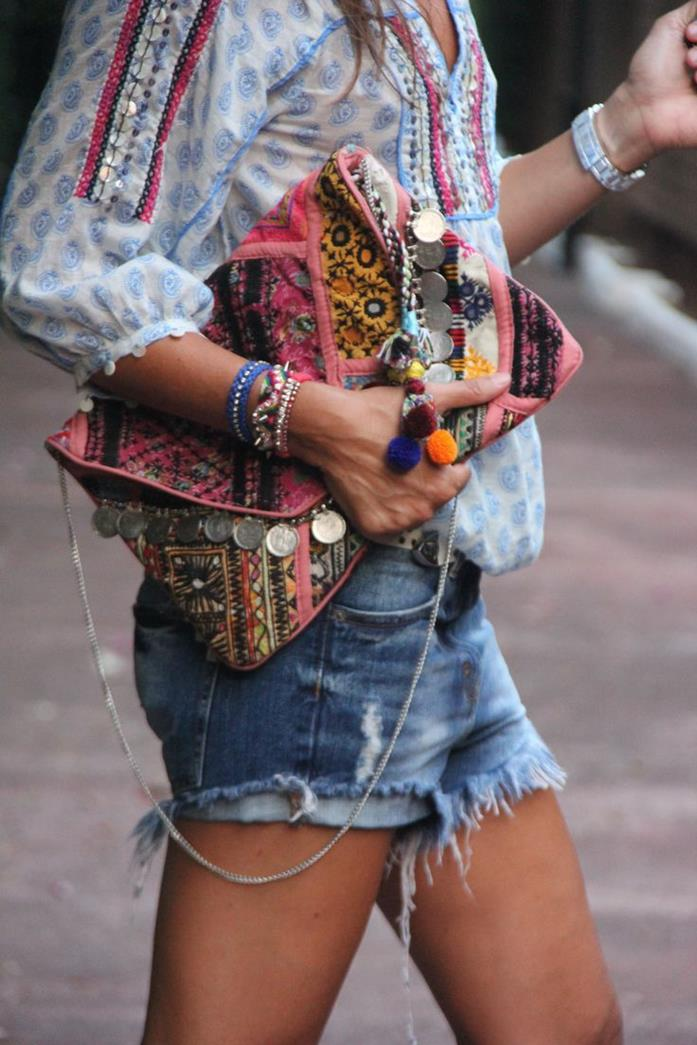 oversized boho fashion clutch, in pink and yellow, with metal beads and thin chainlink handle, held by young woman in shorts and blouse