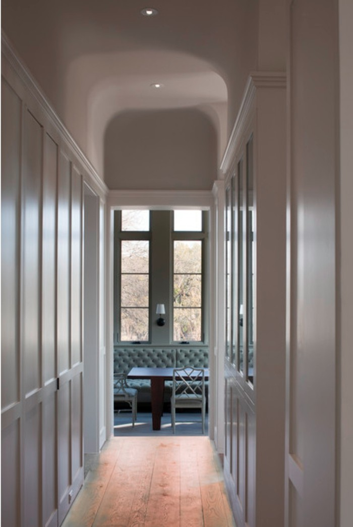 narrow corridor, walls covered with white paneling, solid wooden floor, small ceiling lights, small hallway ideas, another room seen in background