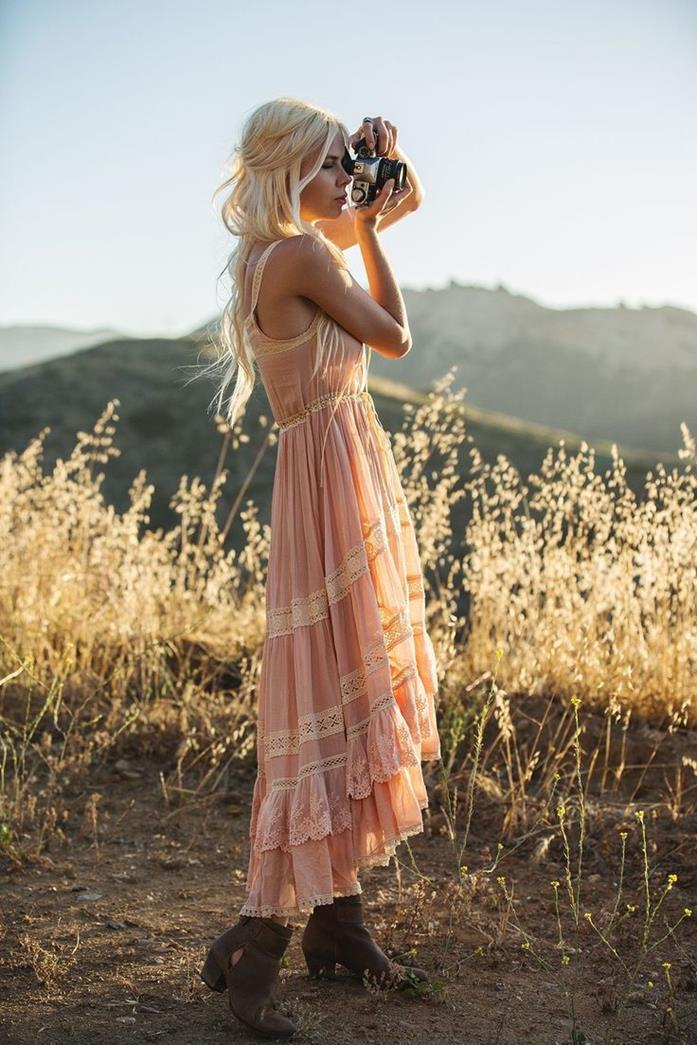 pale pastel pink, tiered sleeveless maxi dress, boho clothing, with frills and lace details, on blonde girl, with brown ankle boots, holding a camera